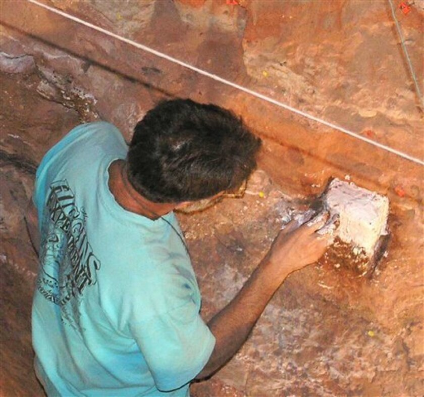 In an undated photo provided by Michael Chazen, Paul Goldberg takes samples in Excavation 1 at Wonderwerk Cave in South Africa. Scientists said Monday, April 2, 2012 that they've found the earliest firm evidence of human ancestors using fire: material about 1 million years old in in Wonderwerk cave. Burned bones and microscopic ash in the dirt suggests fire frequently burned there, apparently under the control of our ancestor Homo erectus, researchers said. (AP Photo/courtesy of Michael Chazan)