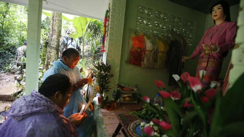 Relatives of 12 young soccer team members and their coach pray at a shrine for their rescue after go
