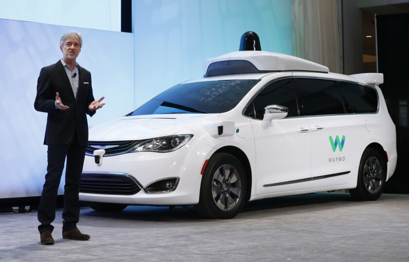John Krafcik, CEO of Waymo, introduces a self-driving Chrysler Pacifica hybrid at the Detroit auto show.
