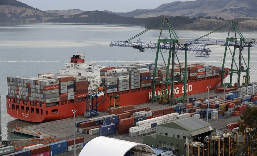 In this June 3, 2020, photo, containers are loaded onto a ship for export at Lyttelton Port near Christchurch, New Zealand. Both Australia and New Zealand announced Wednesday they are starting free-trade talks with the United Kingdom, as each country seeks to rekindle a trading relationship that was severely tested nearly 50 years ago. (AP Photo/Mark Baker)
