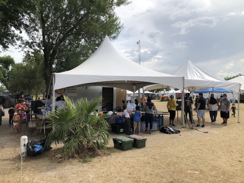 People stand under tents outdoors