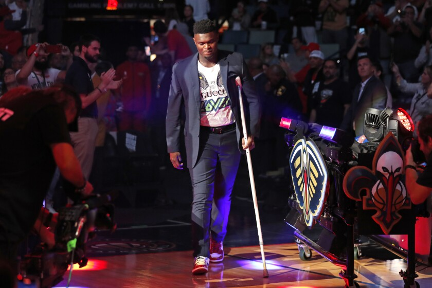 New Orleans Pelicans forward Zion Williamson walk onto the court with a crutch as he is introduced before an NBA basketball home-opener game against the Dallas Mavericks in New Orleans, Friday, Oct. 25, 2019. (AP Photo/Gerald Herbert)
