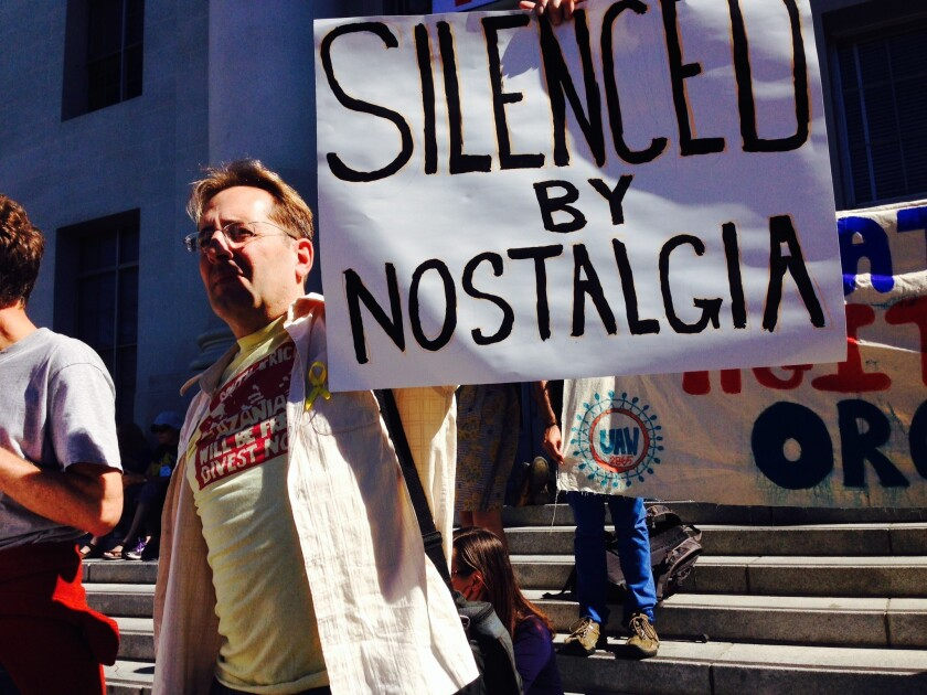 Steve Masover, a UC Berkeley IT employee, holds a sign with a pointed message at the Oct. 1, 2014, rally commemorating the Free Speech Movement's 50th anniversary.