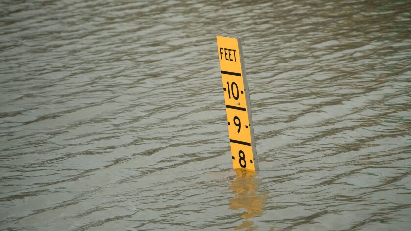 A sign indicates the height of floodwaters on Route 288 in Houston, Texas, in the aftermath of Hurricane Harvey on Sunday. The storm has shut ports in Galveston and Houston, and left cruise ships waiting out the storm in the Gulf of Mexico.