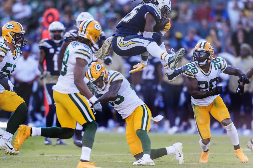 Chargers running back Melvin Gordon leaps over Packers defensive back Chandon Sullivan.