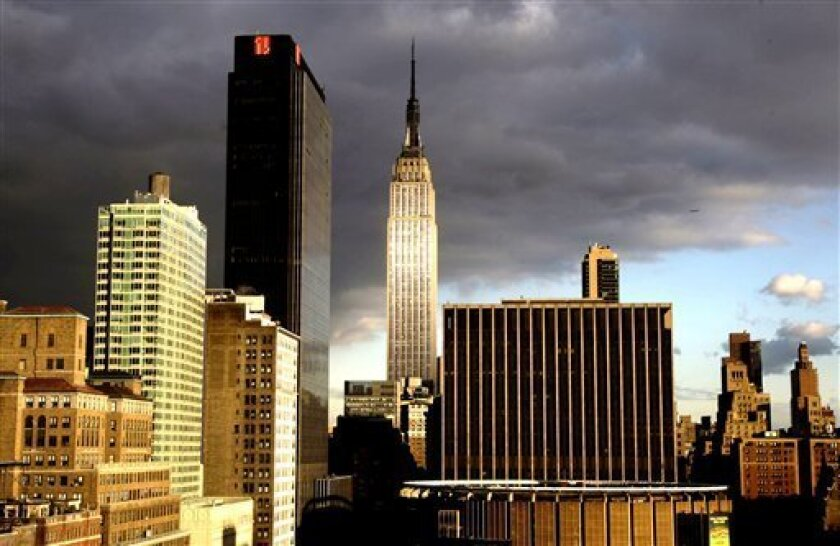 FILE - In this Oct. 29, 2008 file photo, the Empire State Building, center, is illuminated by sunlight against a cloud-darkened sky in New York. When owners of the Empire State Building decided to give it a $120 million environmental makeover, in 2009, they were only partly interested in saving energy.(AP Photo/Kathy Willens, File)