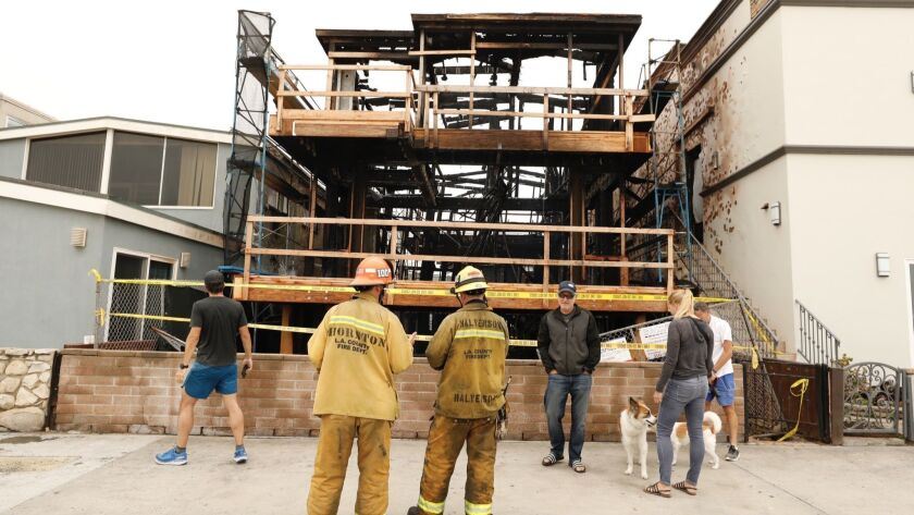 LA County Fire Captain Thornton, left, and Engineer Kevin Halverson inspect a 3- story house under c