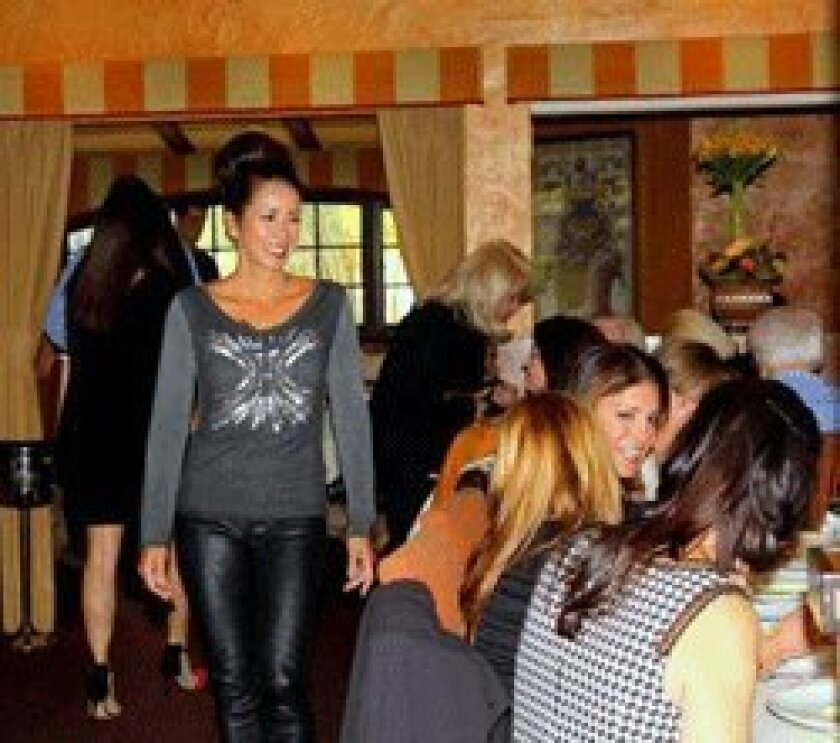 (Left) Sheri Sorenson models fashions from Maggie B, while guests enjoy great friends and great food.