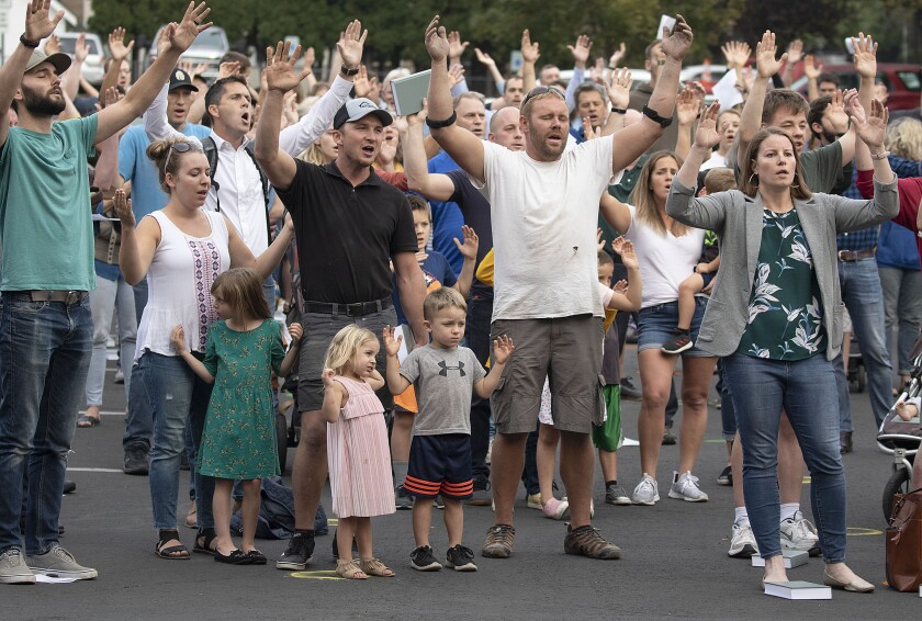 Christ Church members and guests in Moscow, Idaho, sing outside without masks, hands raised, to protest public health orders.