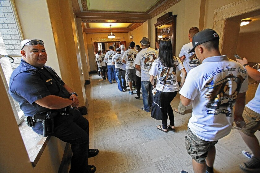 Los Angeles police Officer Luis Ortega, left, watches as other officers head to the City Council chambers. Mayor Eric Garcetti and council members have been trying to hold the line on raises across the city workforce.
