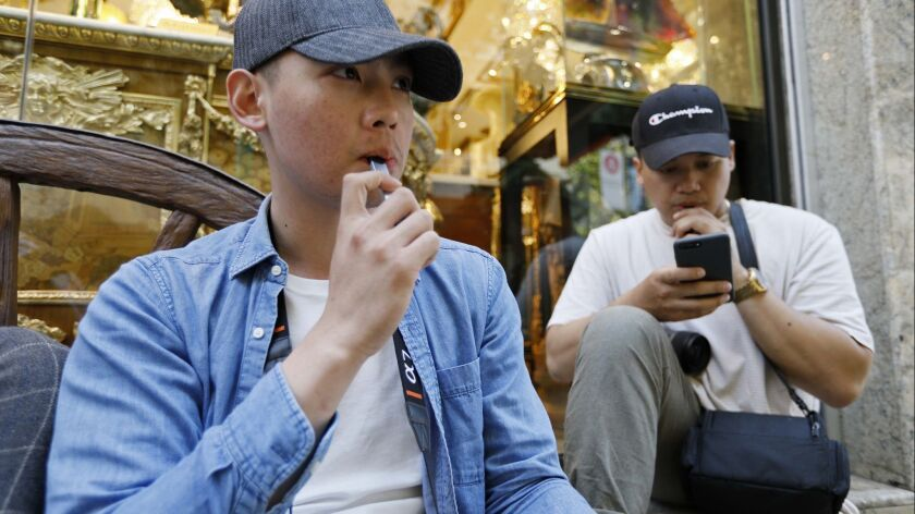 In this Monday, June 17, 2019, photo, Joshua Ni, 24, and Fritz Ramirez, 23, vape from electronic cig