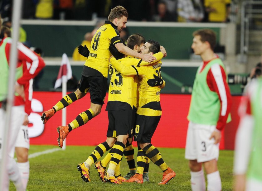 Dortmund's players celebrate their side's third goal during a quarterfinal match of the German soccer cup between VfB Stuttgart and Borussia Dortmund in Stuttgart, Germany, Tuesday, Feb. 9, 2016. (AP Photo/Michael Probst)