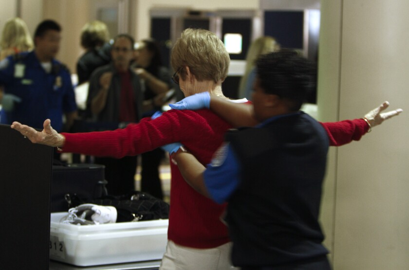 A traveler undergoes a pat-down search at a TSA security checkpoint at Los Angeles International Airport. Federal undercover agents had a 95% success rate at sneaking fake bombs past TSA checkpoints.