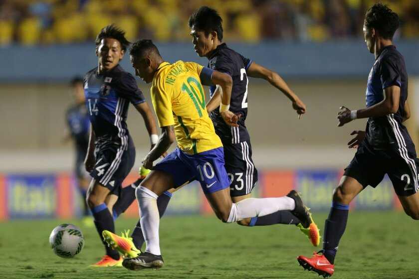 Brazil's Neymar, center, controls the ball past Japan's Sei Maroya, second center, and Japan's Yosuke Ideguche, left, and Japan's Sei Maroya, right, during a friendly soccer game in preparation for the Olympics games, in Goiania, Brazil, Saturday, July, 30, 2016. (AP Photo/Eraldo Peres)