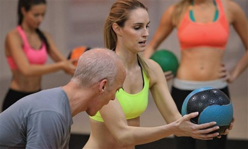 This photo taken Nov. 11, 2009 shows Allison Turner from Cape Girardeau, MO, center, taking instructions from celebrity trainer David Kirsch, left, during the Angel Boot Camp, a model search for Victoria's Secret, New York.  (AP Photo/Bebeto Matthews)