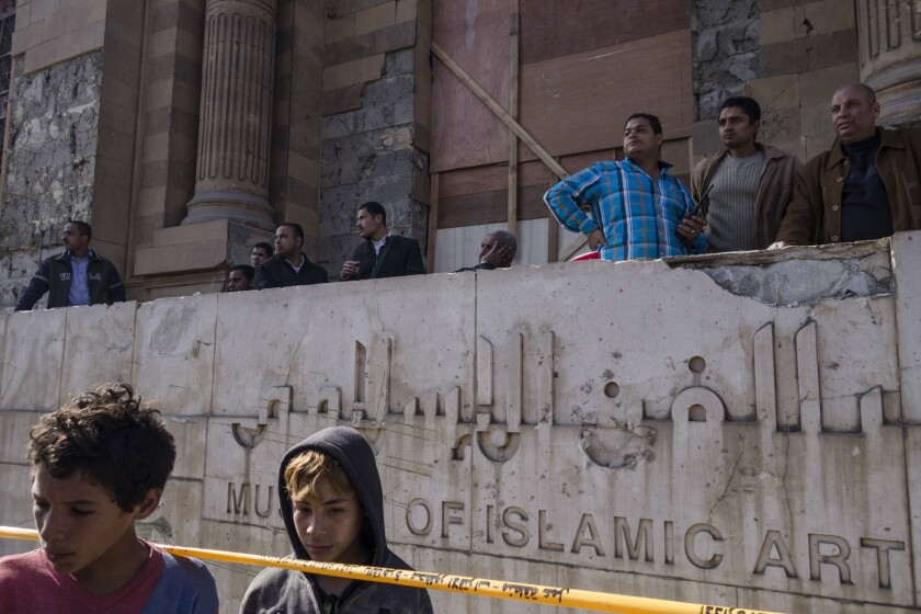 Egyptians stand outside the Museum of Islamic Art in Cairo, which was damaged by a bomb attack at a nearby police building.