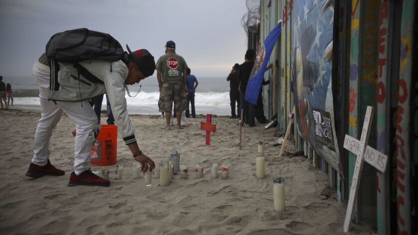 Candles are placed Saturday on the Tijuana side of the U.S.-Mexico border fence in memory of migrants who have died during their journey toward the U.S.