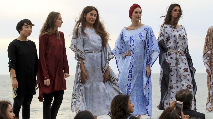Sarah Ansari, center, stands with models at the conclusion of an Artizara fashion show Sunday in Enc