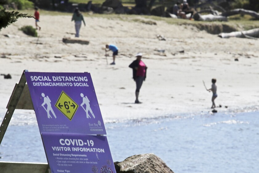 A sign encourages visitors to keep their distance from one another at Crab Cove in Alameda, Calif.