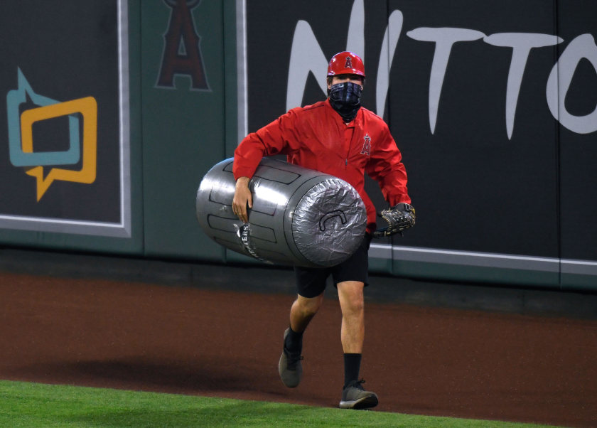 A member of the Angels grounds crew carries an inflated plastic trash can under his arm as he removes it from the field.