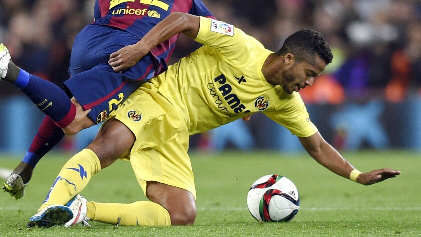 Villareal forward Giovani Dos Santos, right, battles Barcelona defender Dani Alves for the ball during a Spanish Copa del Rey semifinal match in Barcelona on Feb. 11. Dos Santos has played his entire professional career outside of his native Mexico.