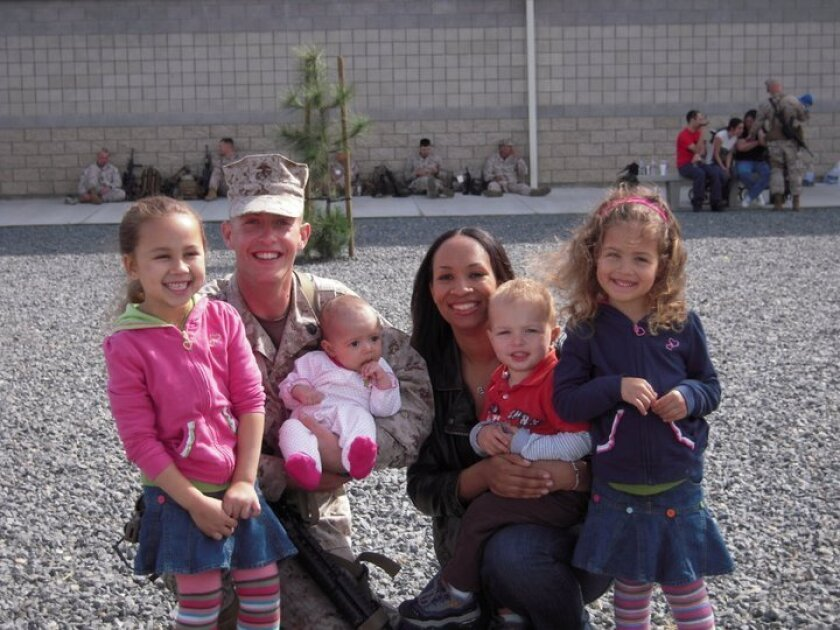 Sgt. Camella Marchett Steedley, at right in civilian clothes, with her husband James Steedley and their children.