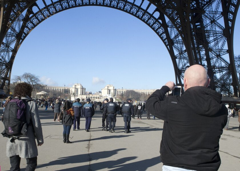 A tourist takes photographs, right, as French police patrol under the Eiffel Tower in Paris, Saturday, Jan. 17, 2015. Since last week's terrorist attacks that killed 17 people in Paris, the swarms of sightseers have thinned below Paris' most visited monument, the Eiffel Tower. Among the tourists th