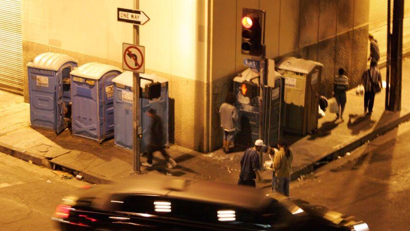 People use portable blue toilets on skid row on Oct. 15, 2005.