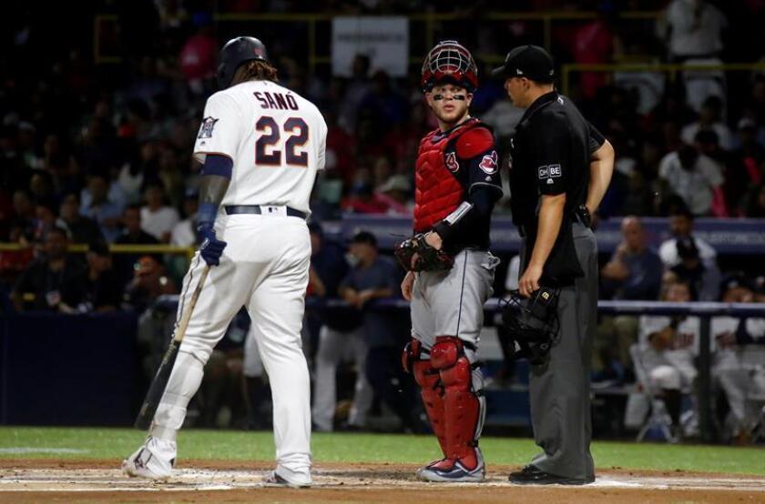 El receptor de los Indios Roberto Pérez (c) habla con el árbitro en el turno al bate de Miguel Sanó (i) de los Mellizos. EFE/Archivo