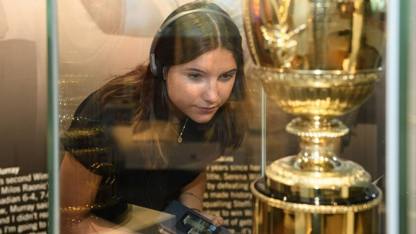 A visitor studies one of the many displays at England's Wimbledon Lawn Tennis Museum