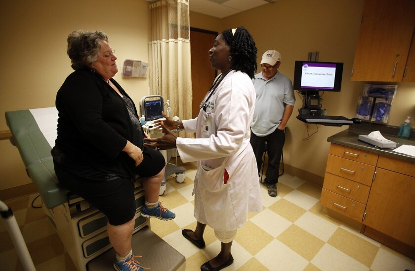 Beth Gladstein of Encinitas, who is uninsured, met with Dr. Tonya Adkins on Tuesday at the Vista Community Clinic as her husband, Dan, stood nearby. / photo by John Gastaldo * U-T San Diego