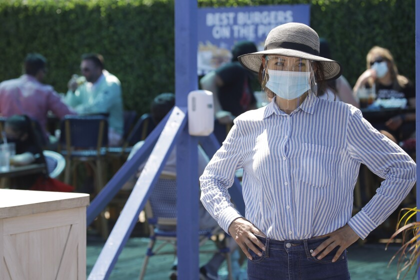 A hostess waits to sit customers on a restaurant at the pier Sunday, July 12, 2020, in Santa Monica, Calif., amid the coronavirus pandemic. A heat wave has brought crowds to California's beaches as the state grappled with a spike in coronavirus infections and hospitalizations. (AP Photo/Marcio Jose Sanchez)