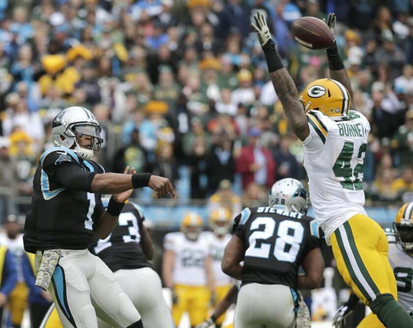 Carolina Panthers' Cam Newton (1) throws a pass under pressure from Green Bay Packers' Morgan Burnett (42) in the first half of an NFL football game in Charlotte, N.C., Sunday, Nov. 8, 2015. (AP Photo/Chuck Burton)