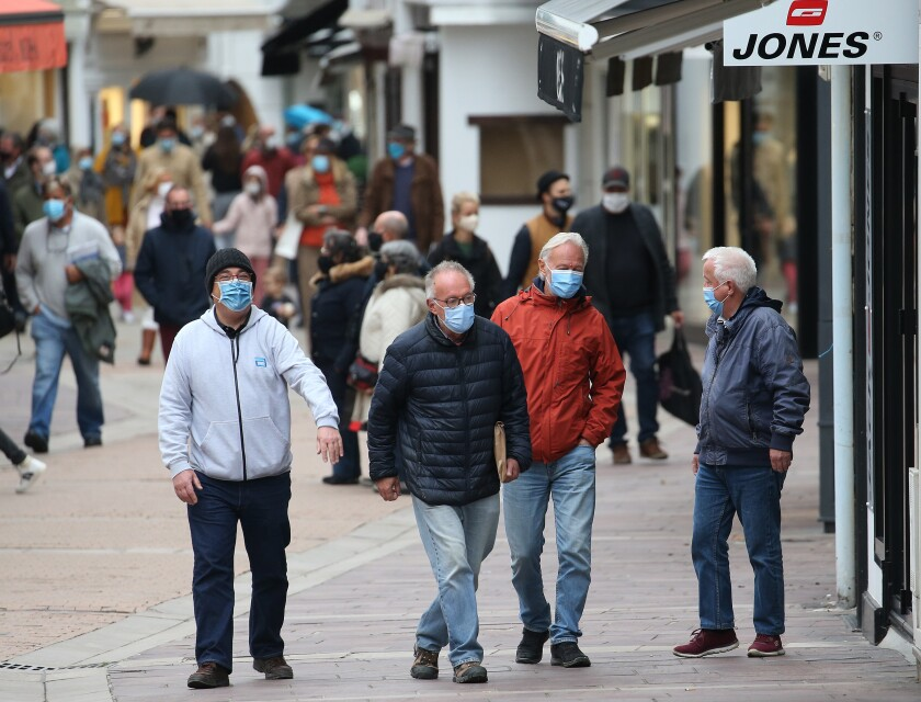 People wearing masks walk down a street in Saint Jean de Luz, southwestern France, Monday, Oct. 12, 2020. Some parts of France have been put on maximum coronavirus alert level, which means shutting down bars, implementing stricter measures in restaurants and limiting private gatherings. (AP Photo/Bob Edme)