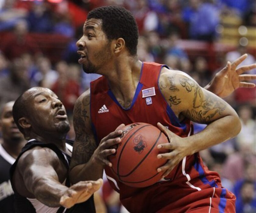 Kansas forward Markieff Morris (21) is covered by Emporia State forward Christian Jackson (4) during the first half of an exhibition college basketball game in Lawrence, Kan., Tuesday, Nov. 9, 2010. (AP Photo/Orlin Wagner)