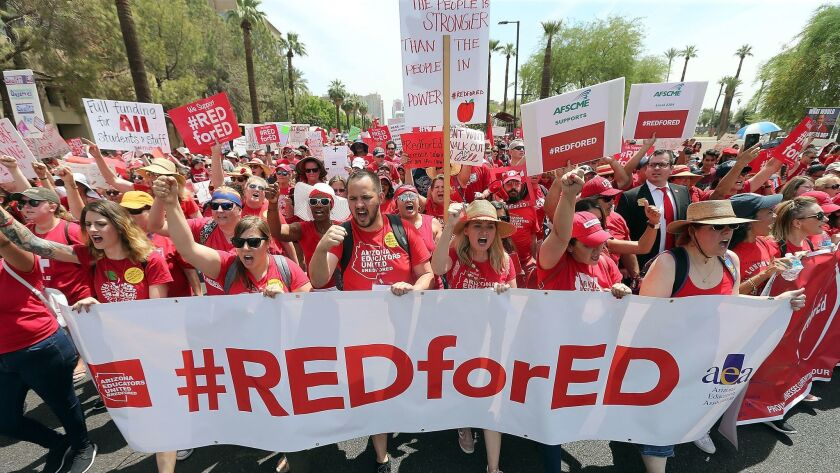 Thousands of Arizona teachers march through downtown Phoenix on their way to the State Capitol as part of a rally for the #REDforED movement.