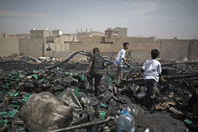 Workers salvage oil canisters from the wreckage of a vehicle oil store hit by Saudi-led airstrikes in Sanaa, Yemen, Thursday, July 2, 2020. (AP Photo/Hani Mohammed)