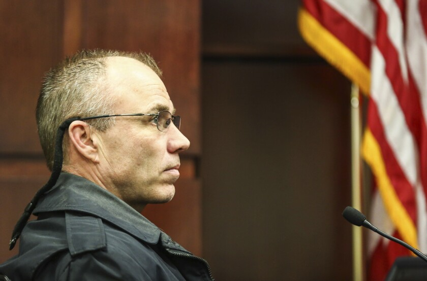 """FILE - In this March 20, 2019 file photo Officer Charles Anderson of the Muskegon Police Department gives his testimony at the Muskegon County Hall of Justice, in Muskegon. Anderson, an ex-Michigan officer fired after a Ku Klux Klan document and Confederate flags were found in his home, says in a report he collected antiques as well as memorabilia linked to """"The Dukes of Hazard"""" TV series. A 400-page report released Monday, Sept. 23, 2019, by the city of Muskegon includes an interview with Anderson. He denies any bias or being a KKK supporter or member. (Kayla Renie/Muskegon Chronicle via AP File)"""