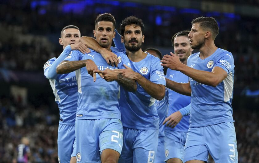 Manchester City's Joao Cancelo, second left, celebrates with Phil Foden, left, Ilkay Gundogan, center, and Ruben Dias, right, after scoring during the Champions League Group A soccer match between Manchester City and RB Leipzig at the Etihad Stadium, Manchester, England, Wednesday Sept. 15, 2021. (Martin Rickett/PA via AP)