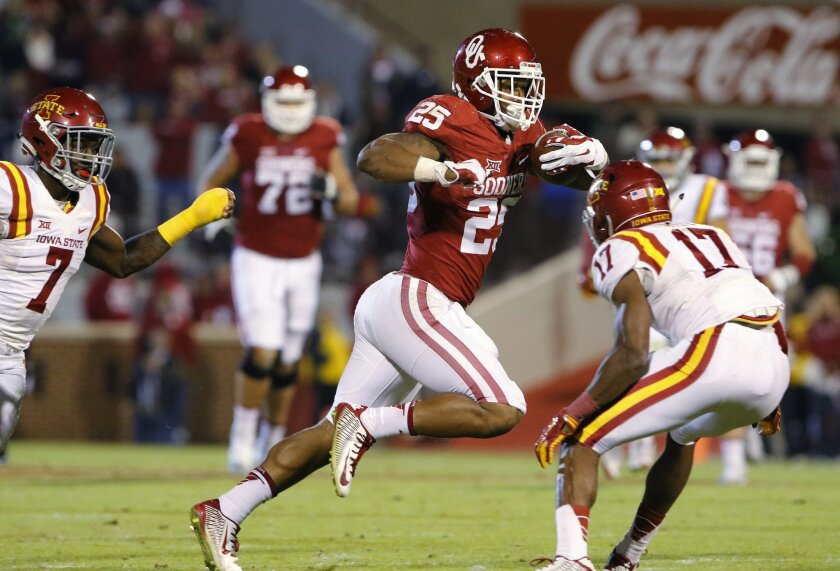 Oklahoma running back Joe Mixon (25) avoids Iowa State defensive back Jomal Wiltz (17) during the fourth quarter of an NCAA college football game in Norman, Okla., on Saturday, Nov. 7, 2015. Oklahoma won 52-16. (AP Photo/Alonzo Adams)
