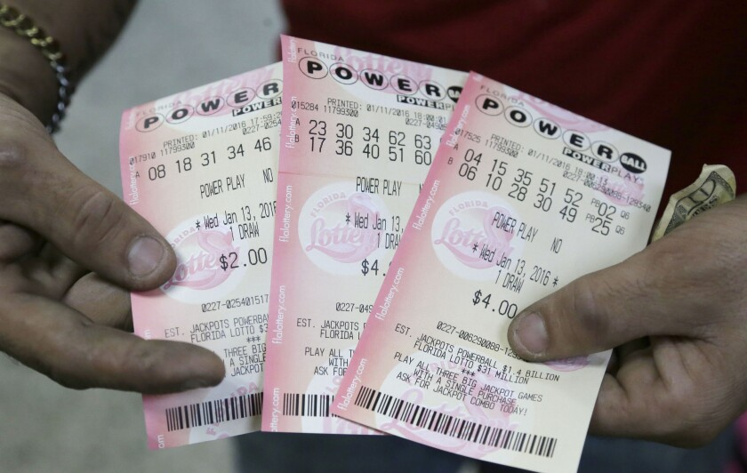 A customer shows his purchased Powerball tickets at a grocery store in Hialeah, Fla., on Jan. 11.