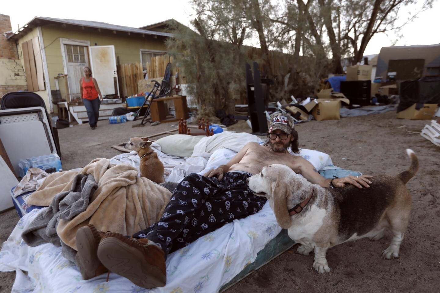 """Dan Tolbert, 62, spends time with his dogs as he and his wife, Ronnie, 60, prepare to bed down for the night on a pair of mattresses in front of their earthquake-damaged home in Trona on July 10. Their night was interrupted when a scorpion crawled on their mattresses and they ended up spending the night in their truck. """"If we keep feeling tremors tomorrow we'll be out here again,"""" Ronnie said."""