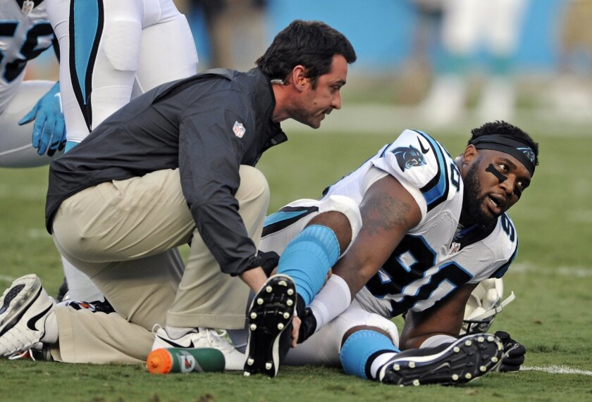 Carolina Panthers' Frank Alexander (90) grabs his leg as a trainer checks on him after being injured during the first half of an NFL preseason football game against the Miami Dolphins in Charlotte, N.C., Saturday, Aug. 22, 2015. (AP Photo/Mike McCarn)