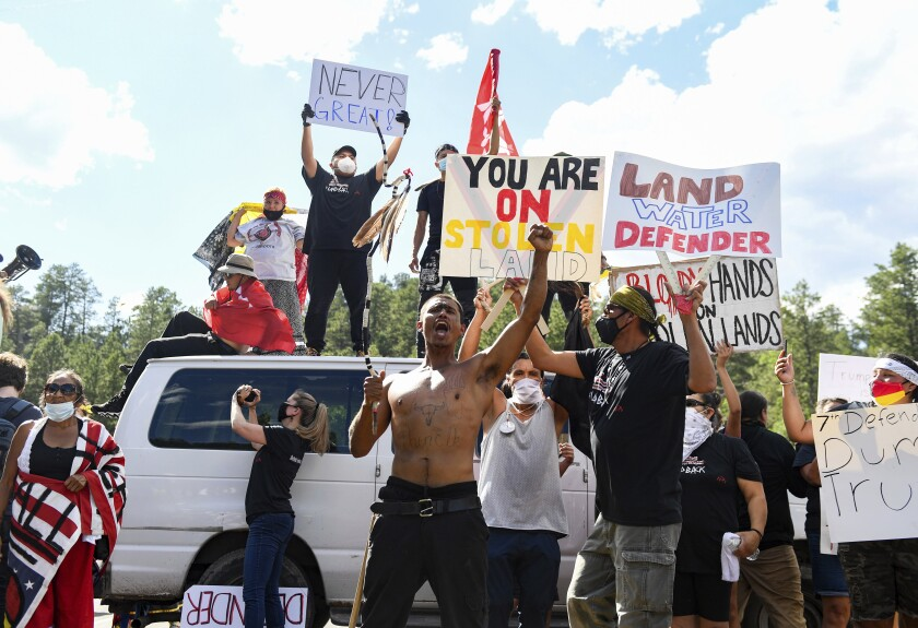Protesters form a blockade of vans and bodies on the highway leading to Mount Rushmore on Friday, July 3, 2020, in Keystone, S.D. President Donald Trump spoke at Mount Rushmore National Memorial. (Erin Bormett/The Argus Leader via AP)