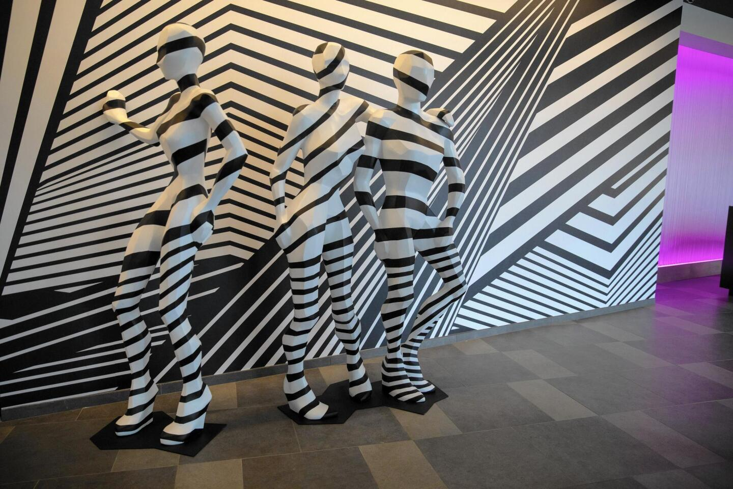 """Eight-foot-tall mannequins covered in black-and-white """"dazzle camouflage"""" greet guests in the lobby of The Rose."""