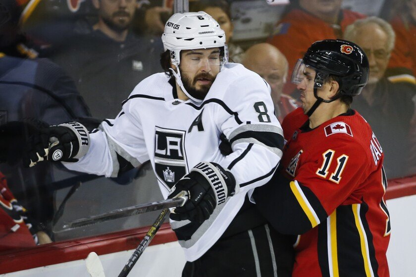 Kings' Drew Doughty, left, is checked by Calgary Flames' Mikael Backlund during the first period on Tuesday in Calgary, Canada.