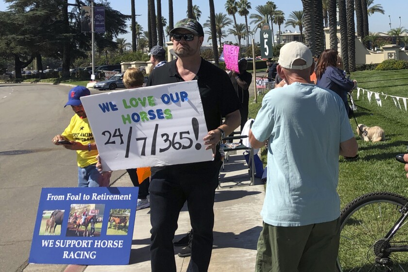 Kentucky Derby-winning trainer Doug O'Neill, center, holds a sign during a rally in support of horse racing and its workers outside the main gate at Santa Anita Park in Arcadia, Calif on Saturday, Oct. 5, 2019. (AP Photo/Beth Harris)