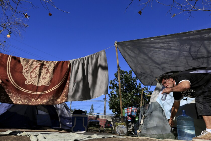 Miguel Hernandez, 50, drinks water outside his tent.