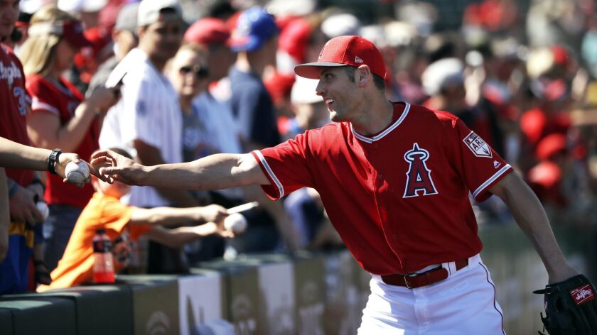 Angels outfielder Peter Bourjos reaches for a ball to sign before a spring training game against the Cubs on March 5 in Tempe, Ariz.