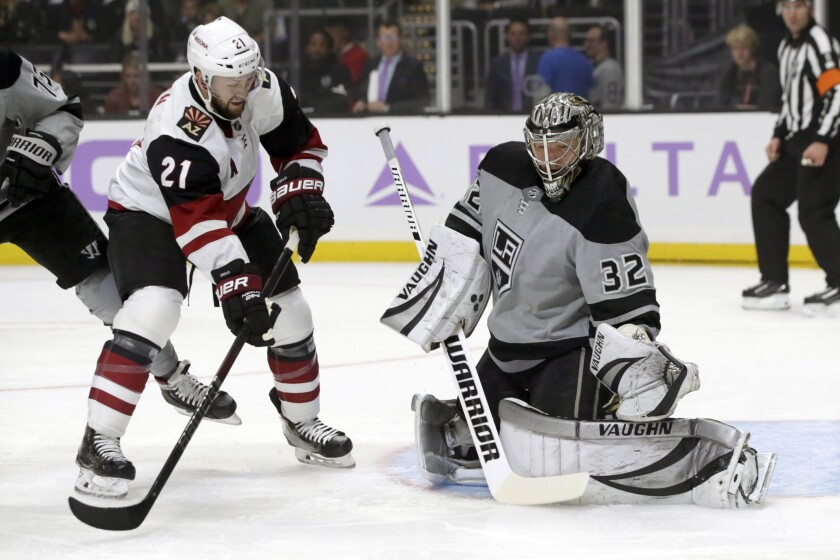 Kings goalie Jonathan Quick, right, catches the puck as Arizona Coyotes center Derek Stepan, left, watches during the first period on Saturday at Staples Center.
